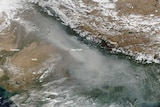 A satellite image shows a dense layer of grey smog over Northern India looming larger than white clouds.