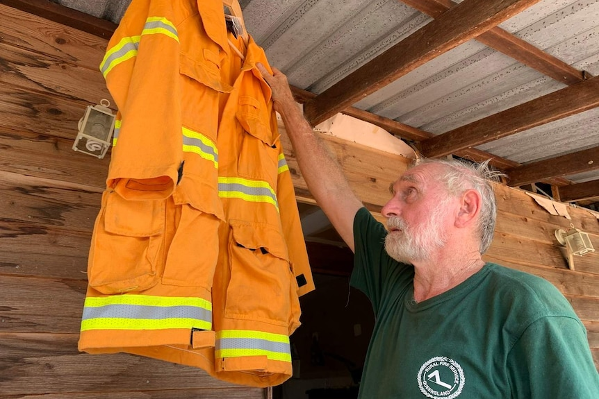Mr Swadling reaches for his RFS uniform which is handing from a rafter under a tin roof.