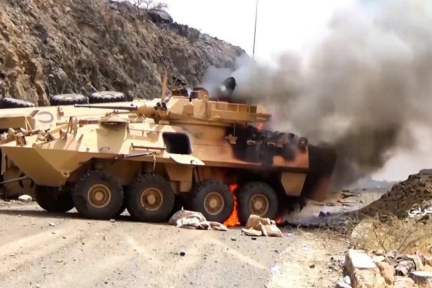 Smoke emits from a sand coloured armoured vehicle which is on fire on a dirt road.
