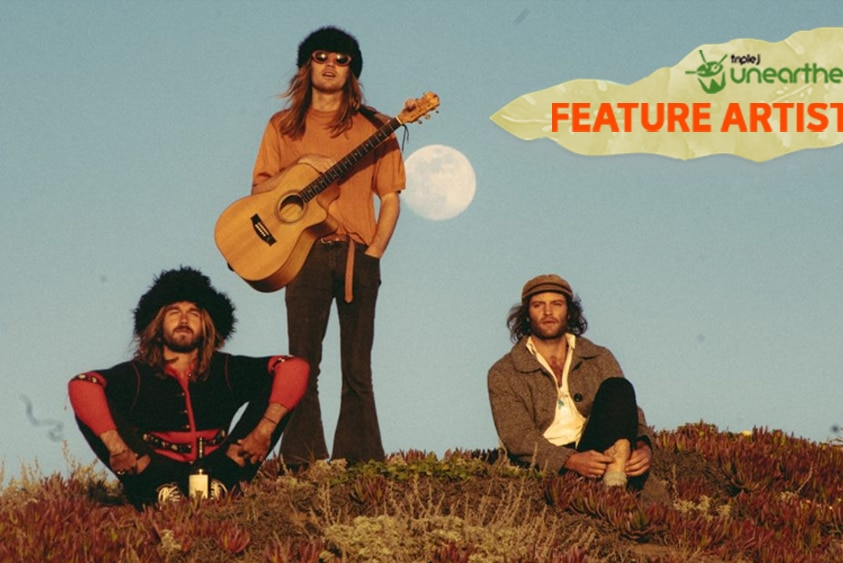 The three members of Le Shiv sit on a grassy hill with the moon behind them and the Feature Artist logo.