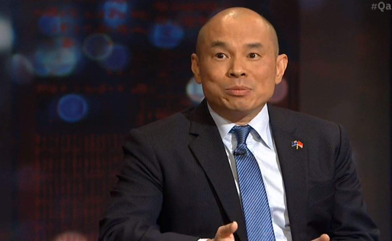 A bald man in a suit and tie with a badge on his lapel looks forward.
