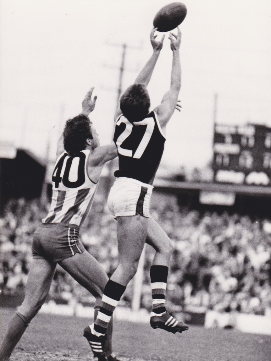An Australian rules player jumps for a mark, the ball at his fingertips.