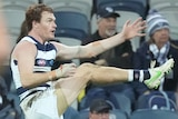 Geelong's Gary Rohan extends his leg mid-kick and watches on.