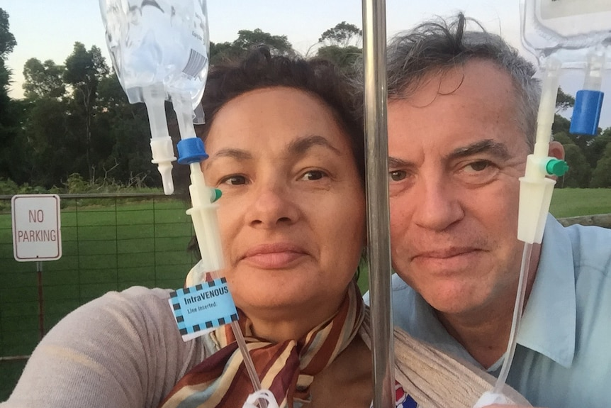 Jill Emberson and her husband Ken with an IV bag and pole.