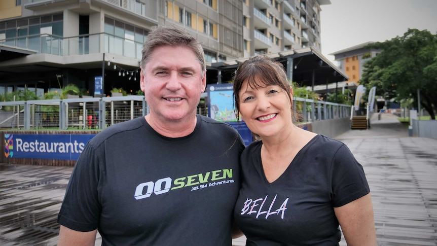Man wearing black 00Seven T-shirt and with woman wearing black Bella Tshirt standing with high-rise apartments behind.