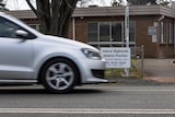 A silver car drives past the Central Highlands General Practice in Ouse, a brown brick building.