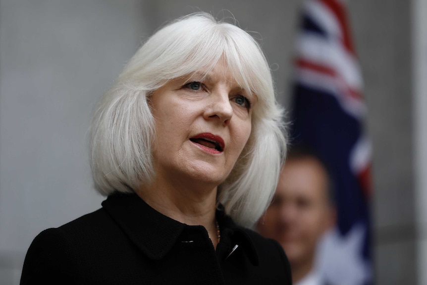 Mid shot of Morgan, wearing a black top, grey hair, standing in front of out-of-focus Australian flag.