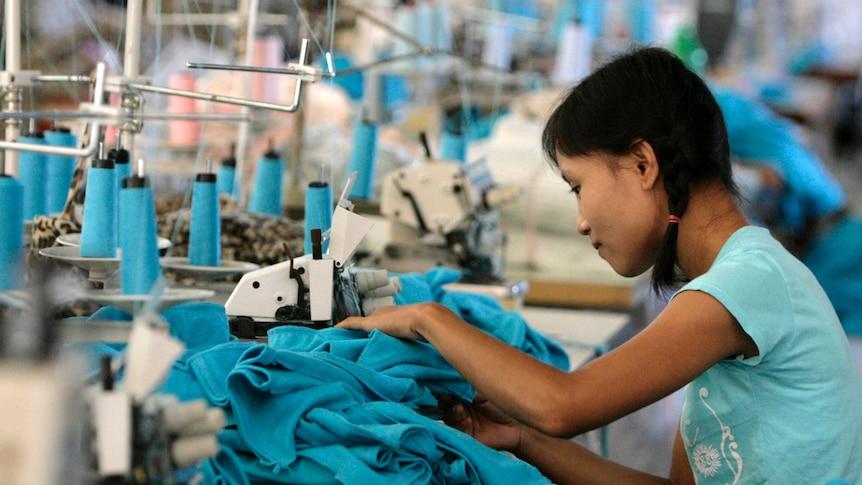 A woman works on a pile of clothes at a sewing machine in a factory