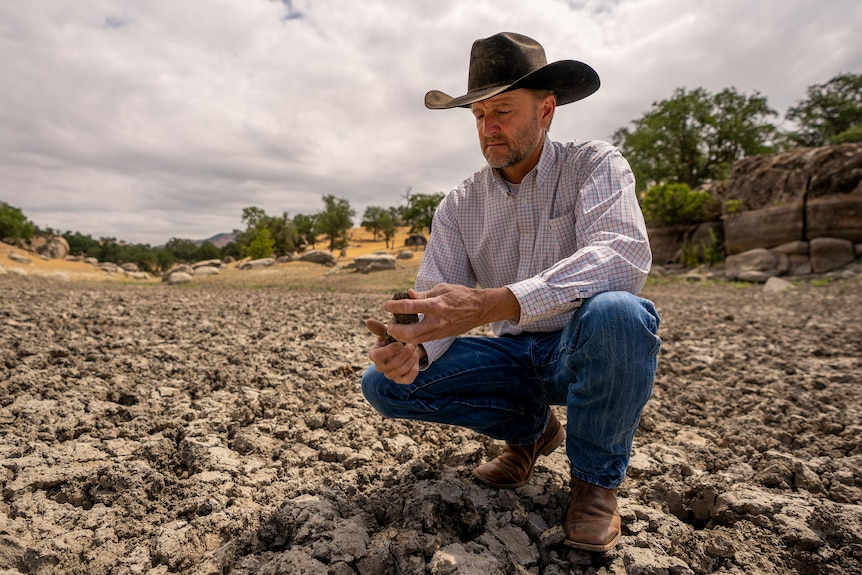 A man in a cowboy hat crouches in a very dry creek bed