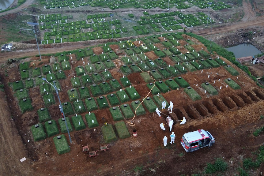 An aerial shot shows workers burying a COVID-19 victim at a dedicated cemetery