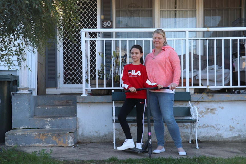 A mum and her daughter out the front of a house