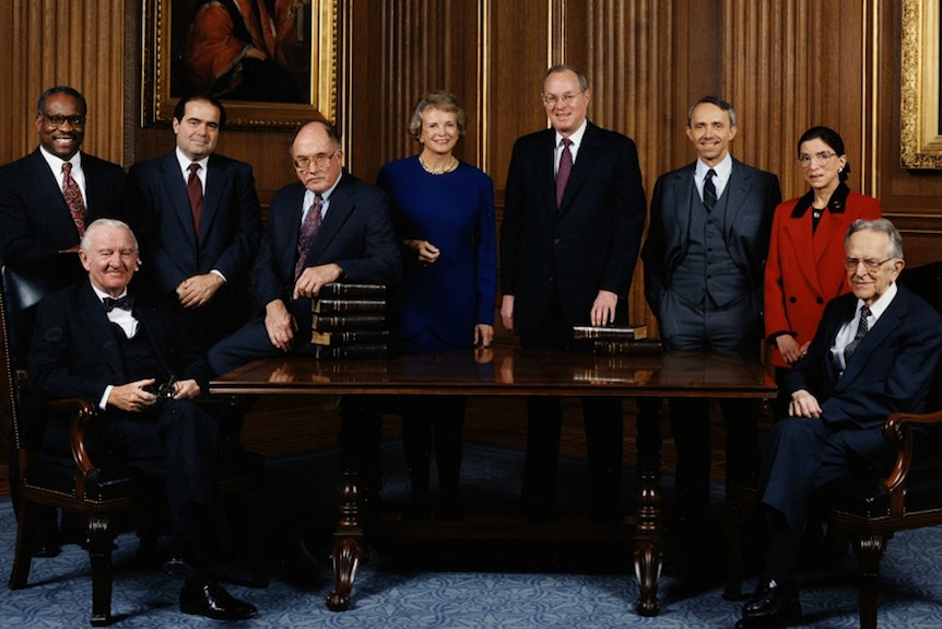 Colour photo of the 1993 Supreme Court Justices posing in front of a wooden table and and room with ornately framed paintings.