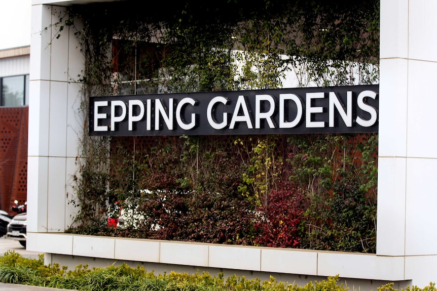Large Epping Gardens sign on vertical garden wall with white tiles on either side