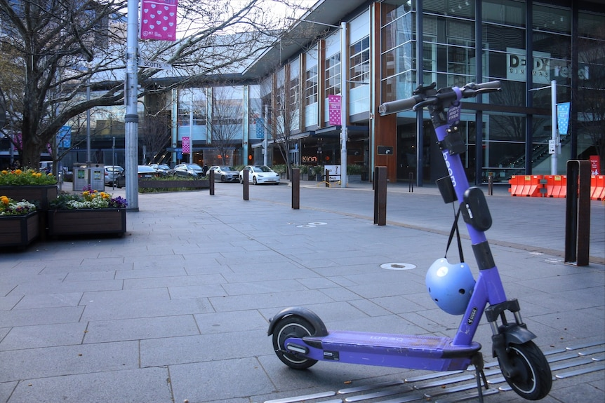 An electric scooter stands with nobody in sight.