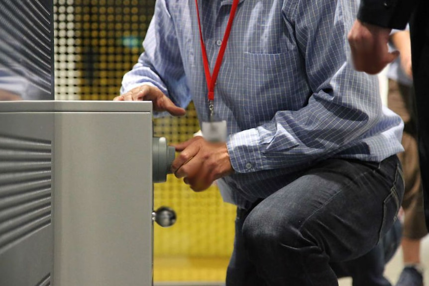 Man kneeling on floor with his hand on a security safe.