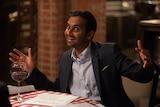 Aziz Ansari sits on a table drinking wine.