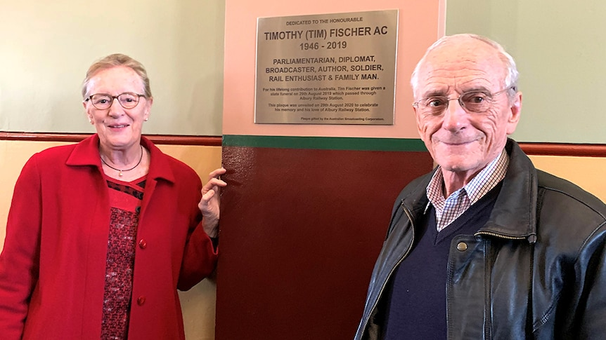 Vicki Baudry and Dr Tony Fischer standing in front of a memorial plaque for Tim Fischer at the Albury Train Station