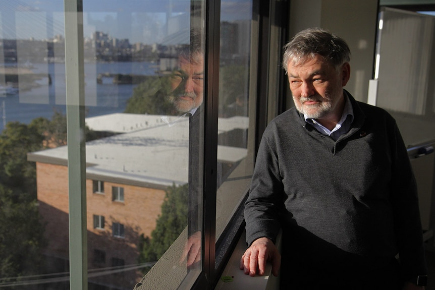Mature aged man stands next to window