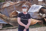 Jessica wears a black t-shirt and white mask, standing in front of burnt and destroyed corrugated iron.