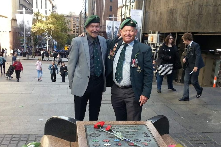 Two men aged in their 70s wear war medals and stand in front of memorial