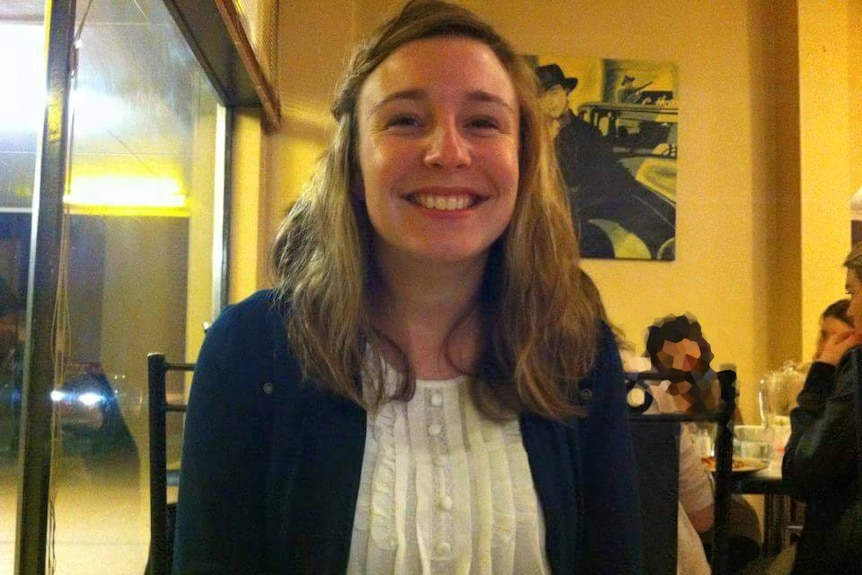 Smiling photo of Stephanie Scott wearing a dark jumper over a white shirt with fine vertical frills