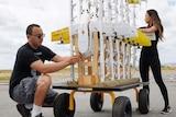 Two people help arrange drones on a trolley