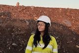 A woman in a yellow shirt, hard white safety hat and clear safety goggles stands in front of a pile of red dirt and rocks.