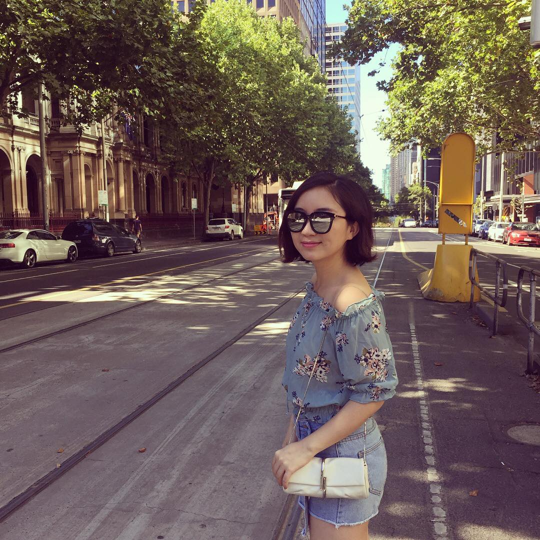 A young Chinese lady, wearing sunglasses, about to cross the road.