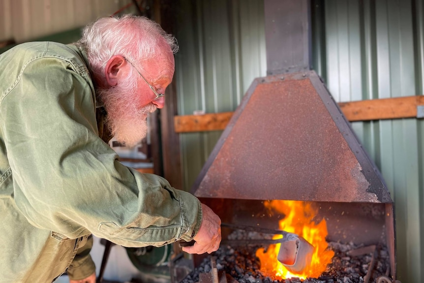 Man holding tongs with a cowbell on the end into a fire.