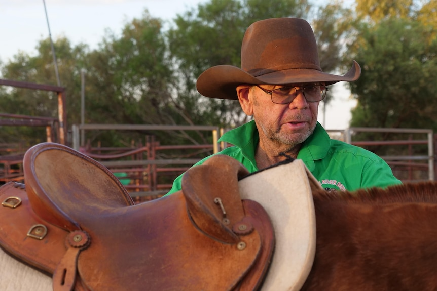 Man wearing a hat and green shirt standing next to a horse.