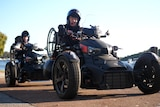 Two mean on three wheel motorbikes wearing helmets, with wheelchairs stored on the back
