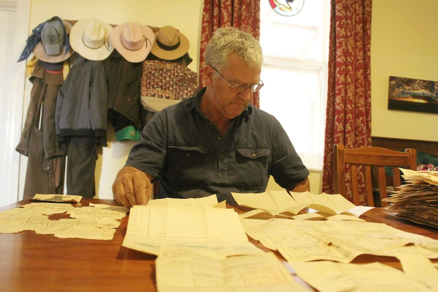 Pastoralist Simon Hilder sits at a table with old documents spread out in front of him.