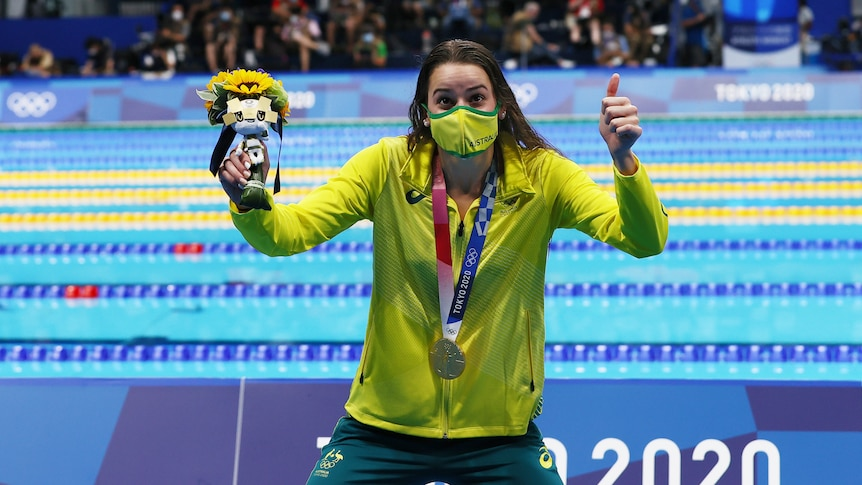 Wearing her gold medal and holding the Tokyo mascot, Kaylee McKeown gives a big thumbs up