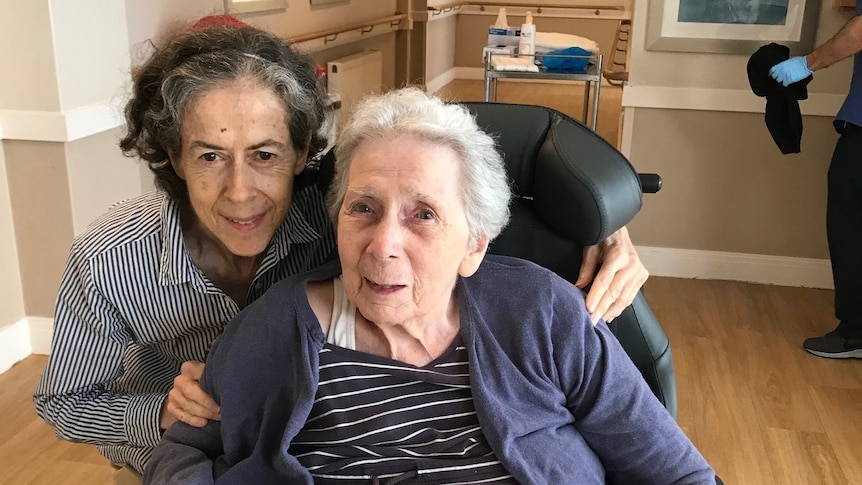 Patricia is sitting down and Therese is crouching behind her will arms around her chair.