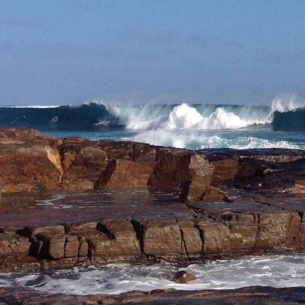 A rocky shoreline with large crashing waves in the background.