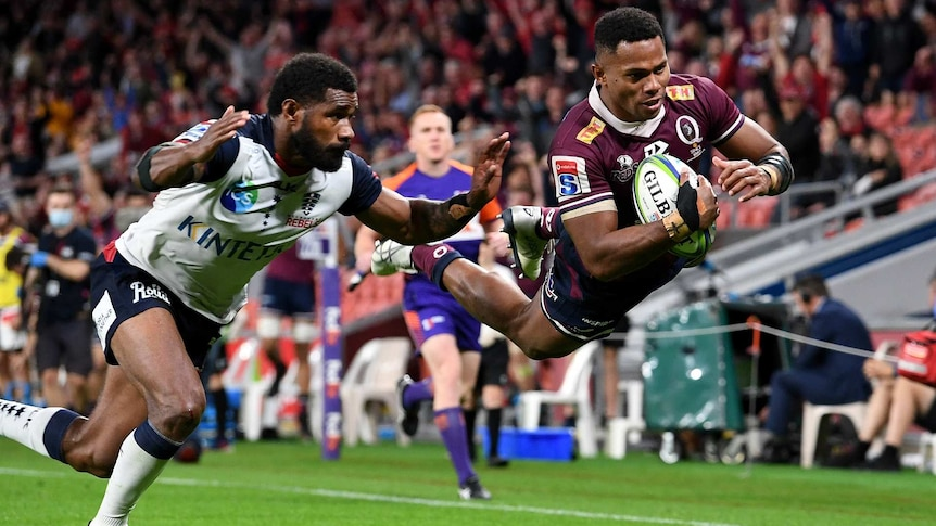 Filipo Daugunu of the Queensland Reds dives in for a try infront of a crowd at suncorp stadium in brisbane