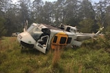 A helicopter tilts on its side, with no rotors, in a clearing surrounded by trees.