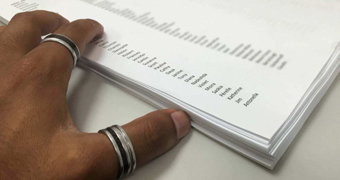 A hand next to a list of names on paper