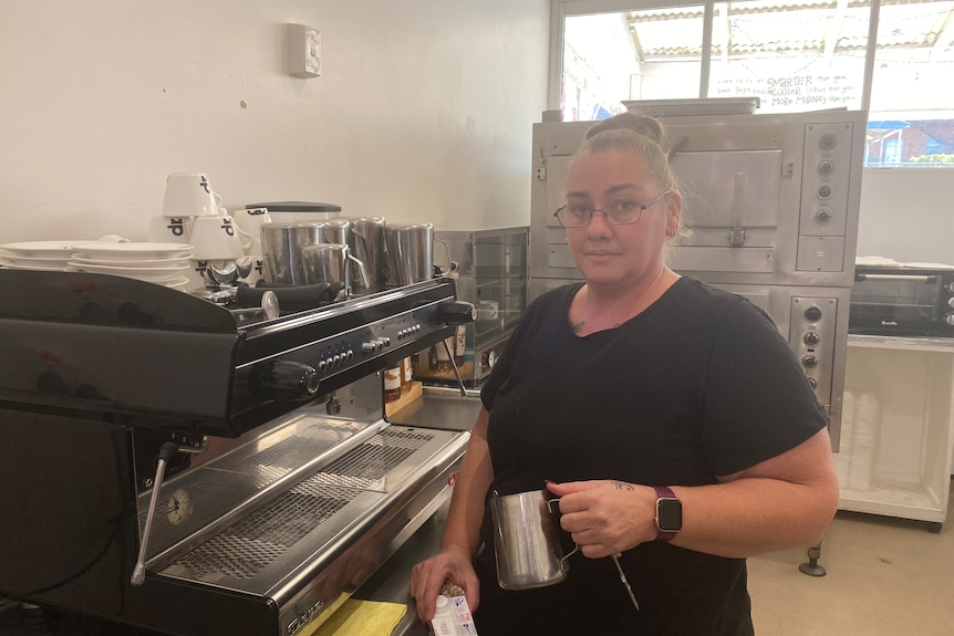 A woman in a black shirt with glasses standing next to a coffee machine and holding a milk jug
