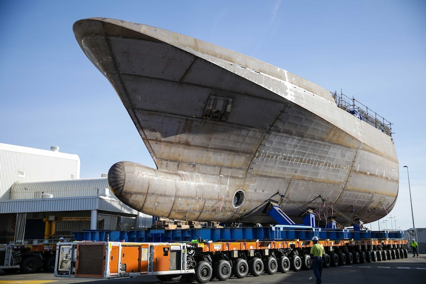 The bow section of a boat is seen on the back of a truck