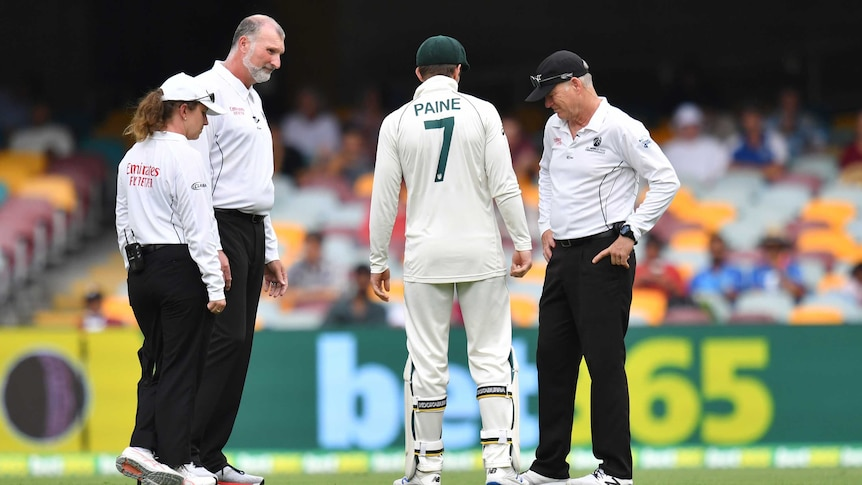 Tim Paine speaks with three match officials out in the middle of the Gabba during a rain delay.