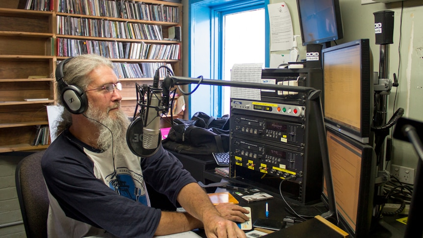 A man with grey hair and a long beard sits behind a radio studio desk, headphones on.