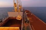 Large ship carrying red bauxite on ocean at dusk.