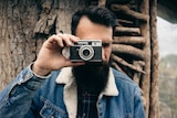 A man with coiffed black hair and a fashionable beard holds a vintage camera.
