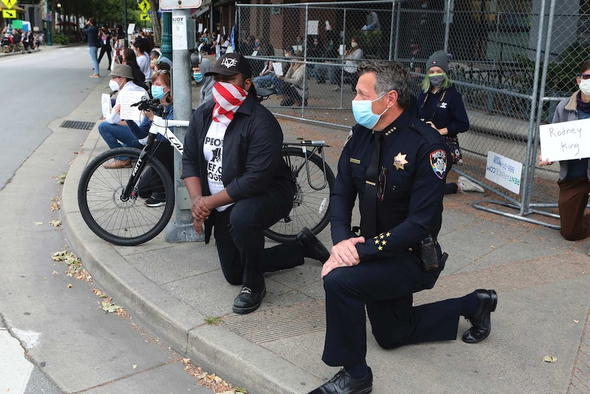 Protesters kneel against police violence against African-Americans following the death of George Floyd.