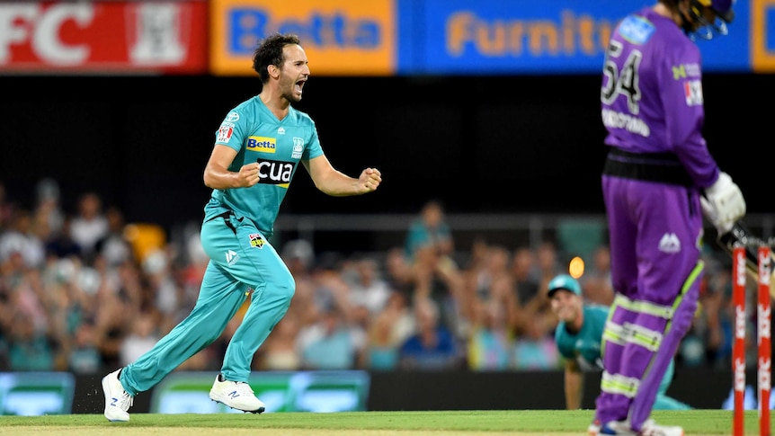 A Big Bash bowler runs away with fists clenched after getting a wicket on debut for Brisbane Heat.