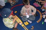 Two unidentified boys playing with trains on floor at child care centre, Canberra. Generic.