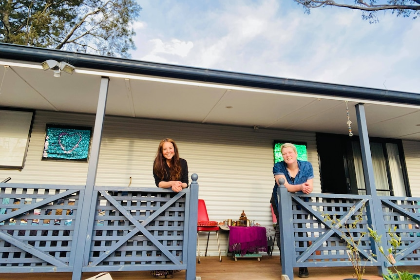 Two women standing on a verandah for a story on home ownership.