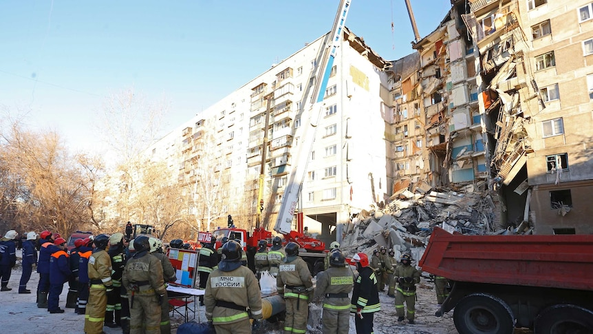 On a clear sky, a crane lifts concrete debris from an apartment block which has partially collapsed with firefighters looking on