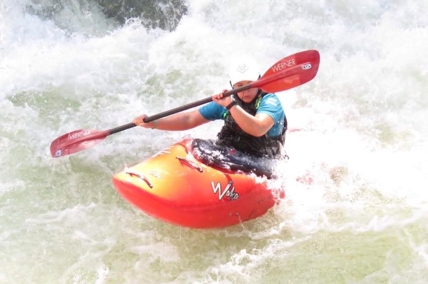 A woman navigates  in an orange kayak with an orange and black paddle